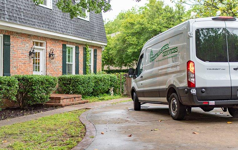 a pestmaster services vehicle parked in driveway in front of home