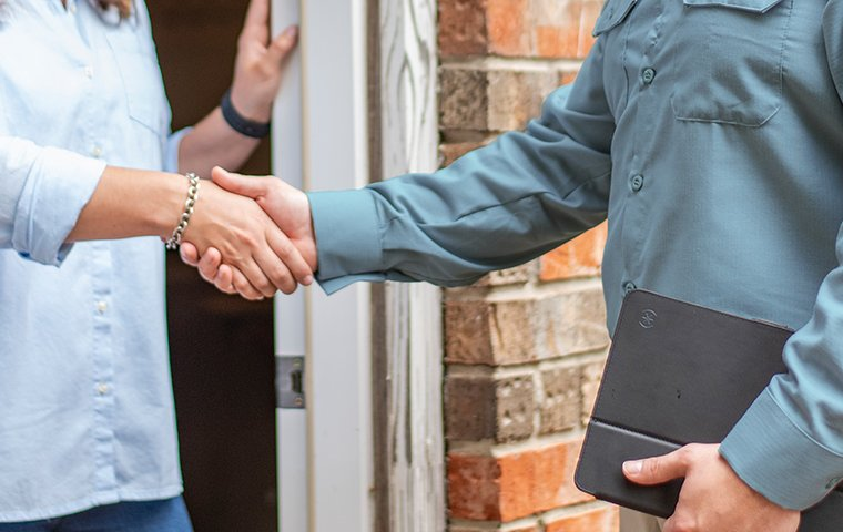 a friendly pest tech shaking hands with homeowner at front door