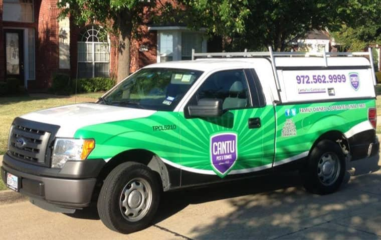a cantu pest control company car parked outside of a home in houston texas