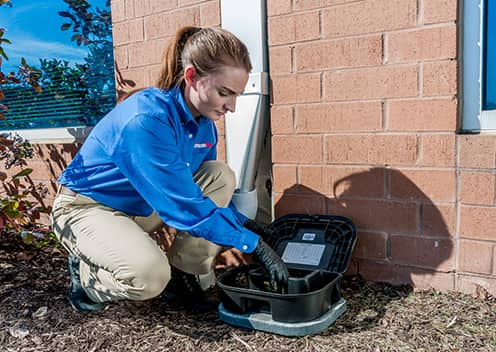 a technician setting up a rodent bait station outside a home in crofton maryland