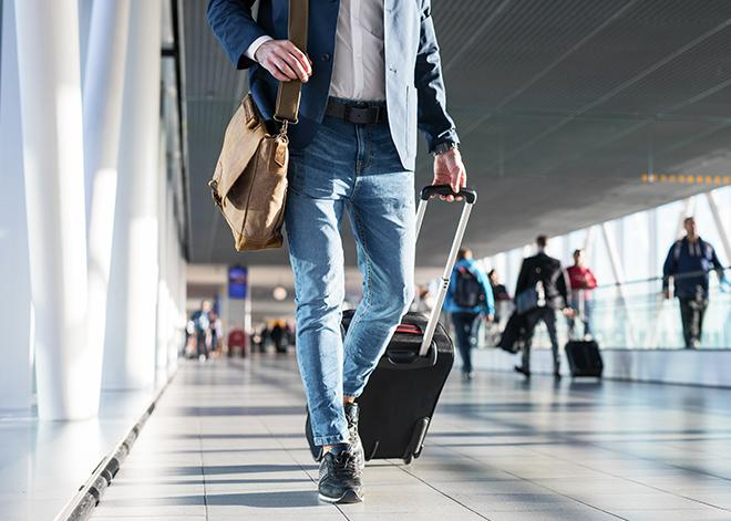 a man walking with his luggage through an airport in washington dc