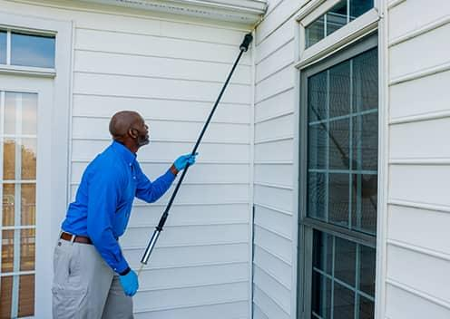 a technician performing an exterior home treatment in colesville maryland