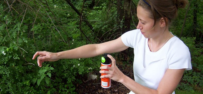 woman applying bug spray correctly