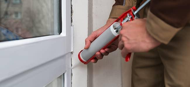 homeowner sealing cracks to prevent spiders
