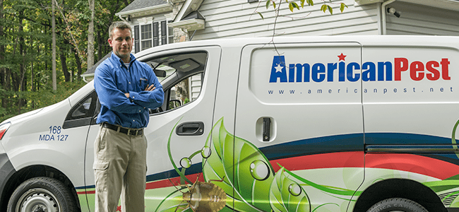 residential pest control technician standing near vehicle