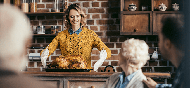 a middle aged woman prepares to carry a cooked turkey to the dinner table for her guests