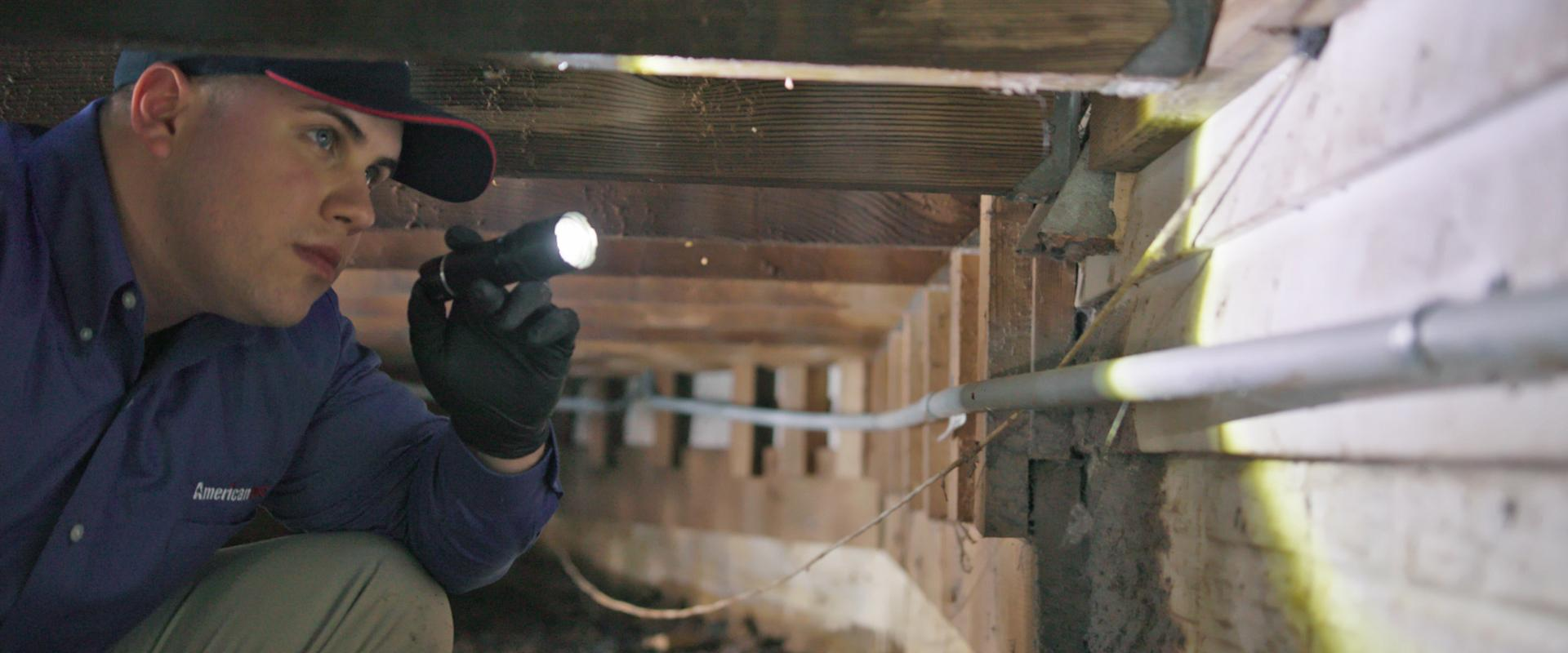 tech inspecting crawl space under home