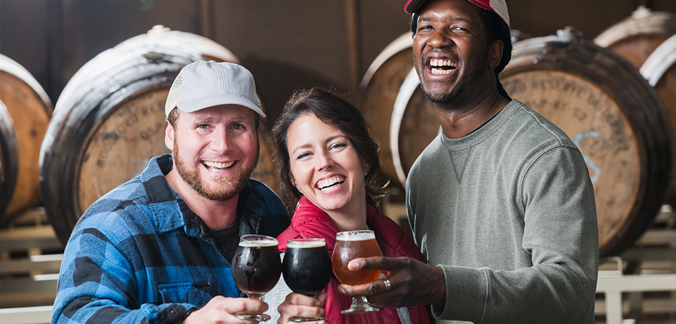 three people enjoying beer from local md brewery