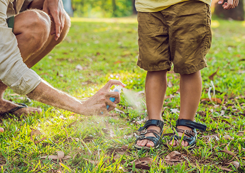 a parent spraying their childs feet with repellent in virginia