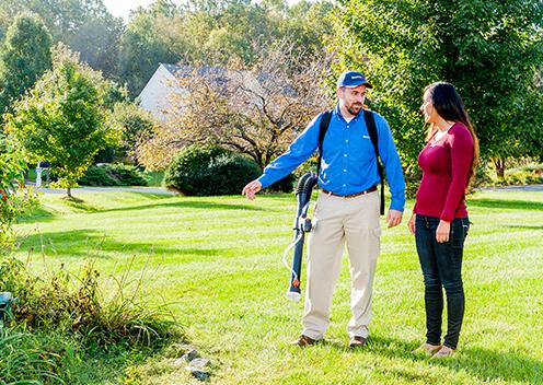 a technician inspecting a yard with a customer in maryland