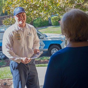 a pest technician speaking with a customer