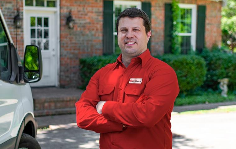 a pest control service technician posing in front of a home in carlsbad california