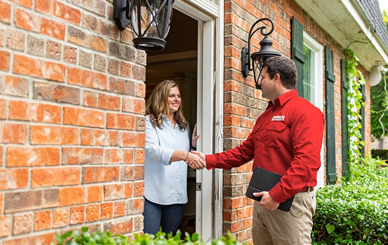 a pest control service technician greeting a residential homeowner in norco california