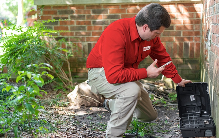 a pest control service technician applying pest control treatments to the exterior of a home in murrieta california