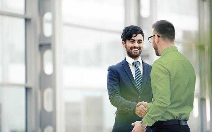 technician shaking hands with businessman
