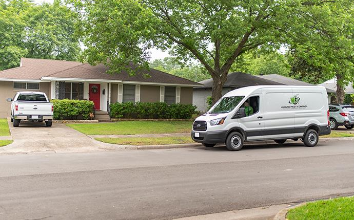 pest control company van pulling up to house
