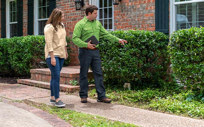 pest control technician and homeowner inspecting exterior