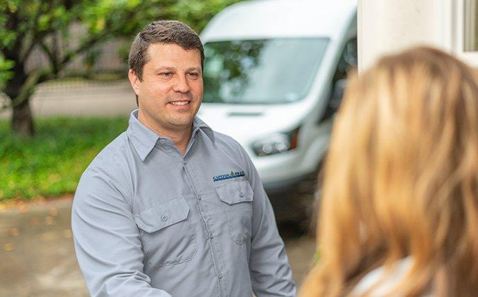 a capitol pest bed bug control expert discussing ongoing treatment with a happy customer