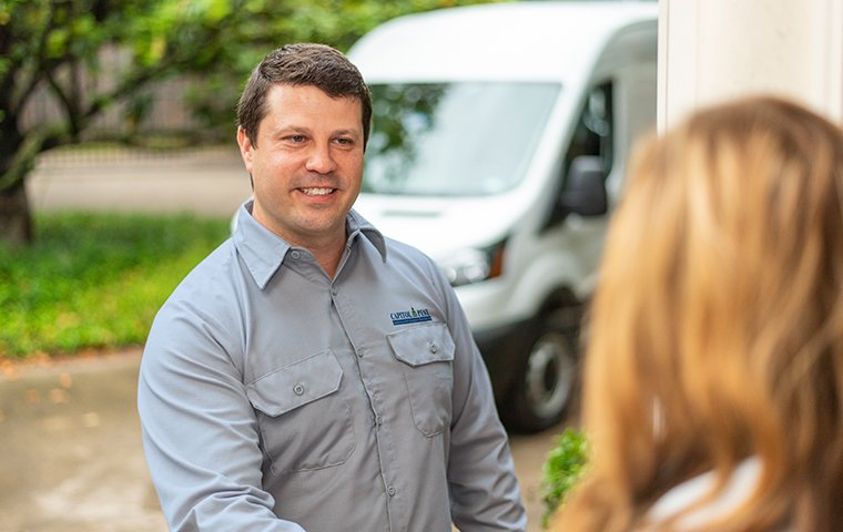 a pest technician greeting a customer in front of her home in washington dc