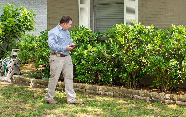 a pest technician inspecting the exterior of a home in washington dc