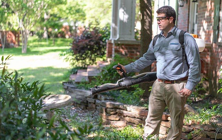 a pest technician treating the exterior of a home for mosquitoes in washington dc