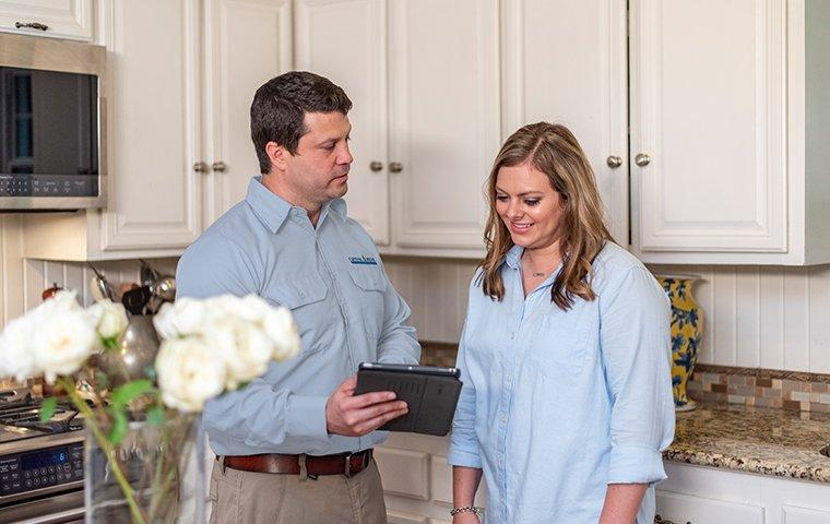a pest technician meeting with a customer in her home in washington dc