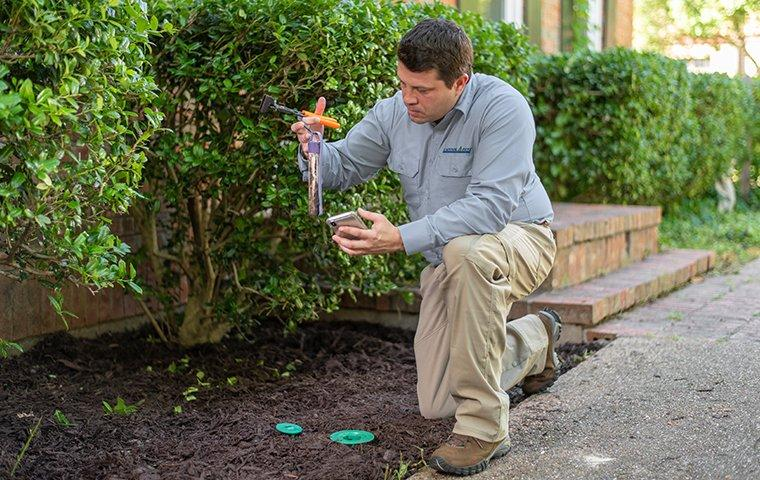 a pest technician installing termite bait stations at a home in washington d.c.