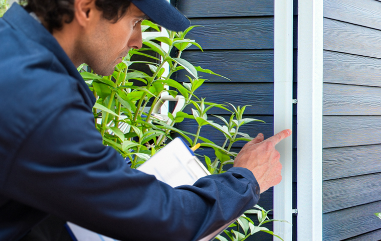 a heritage pest control service technician inspecting a home in franklin lakes new jersey