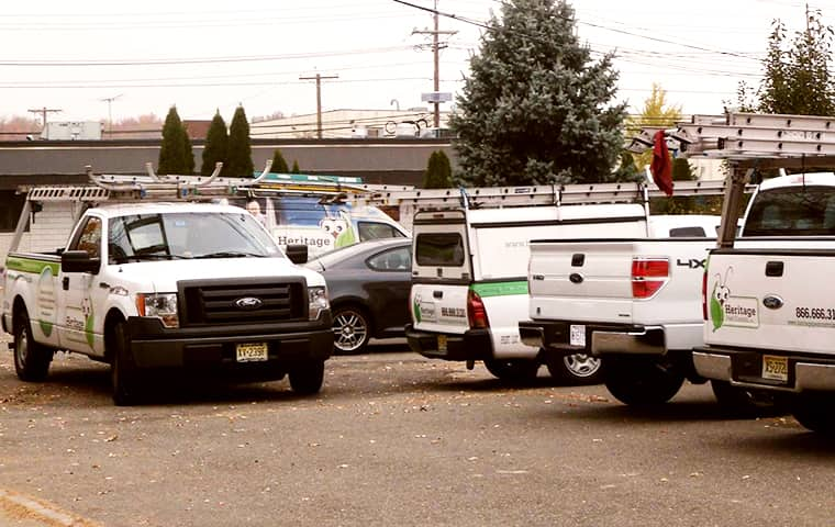heritage pest control company vehicles parked in a pompton plains parking lot
