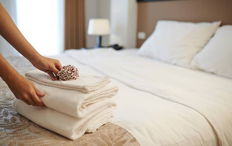 a hospitality worker folding towels inside a hotel room in pompton lakes new jersey