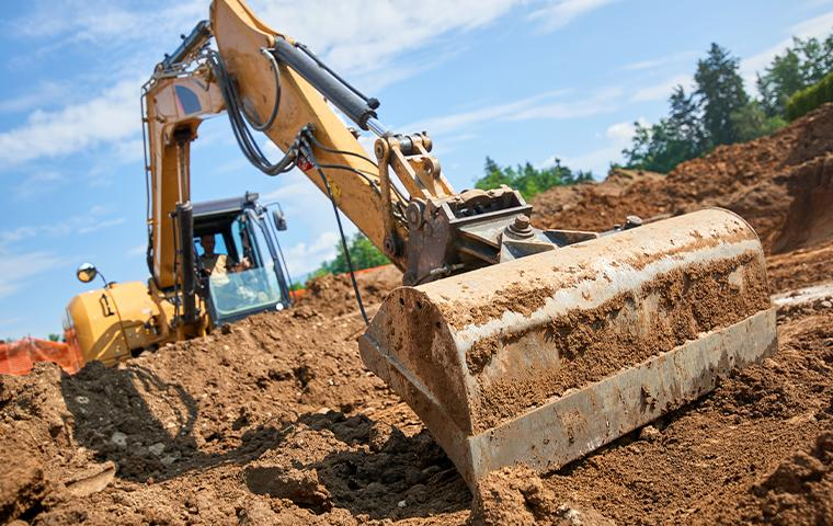 construction vehicle digging out house foundation