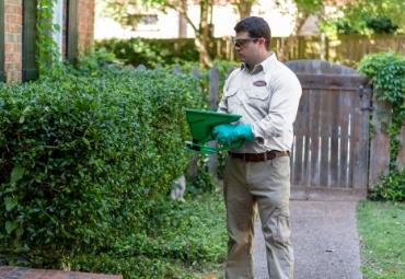 romney pest control technician treating yard for pests