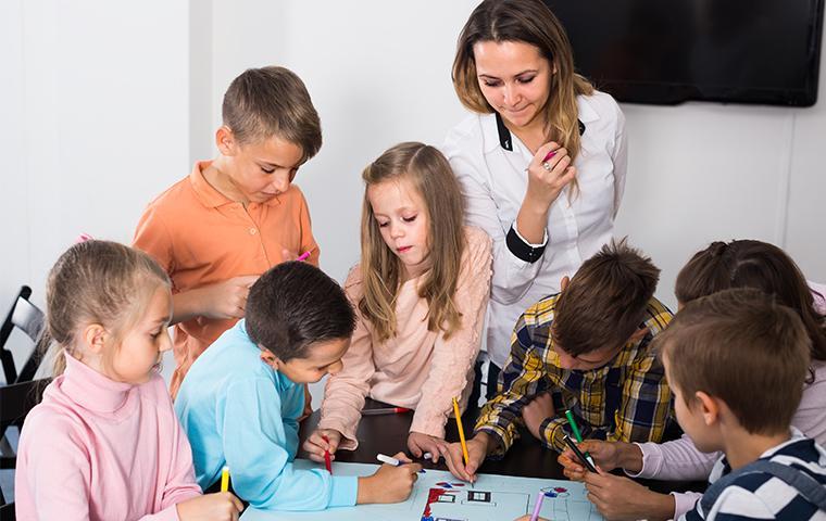 teacher teaching small children in classroom