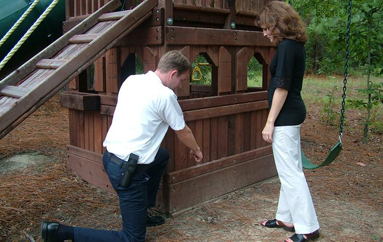 tech inspecting with homeowner near play set