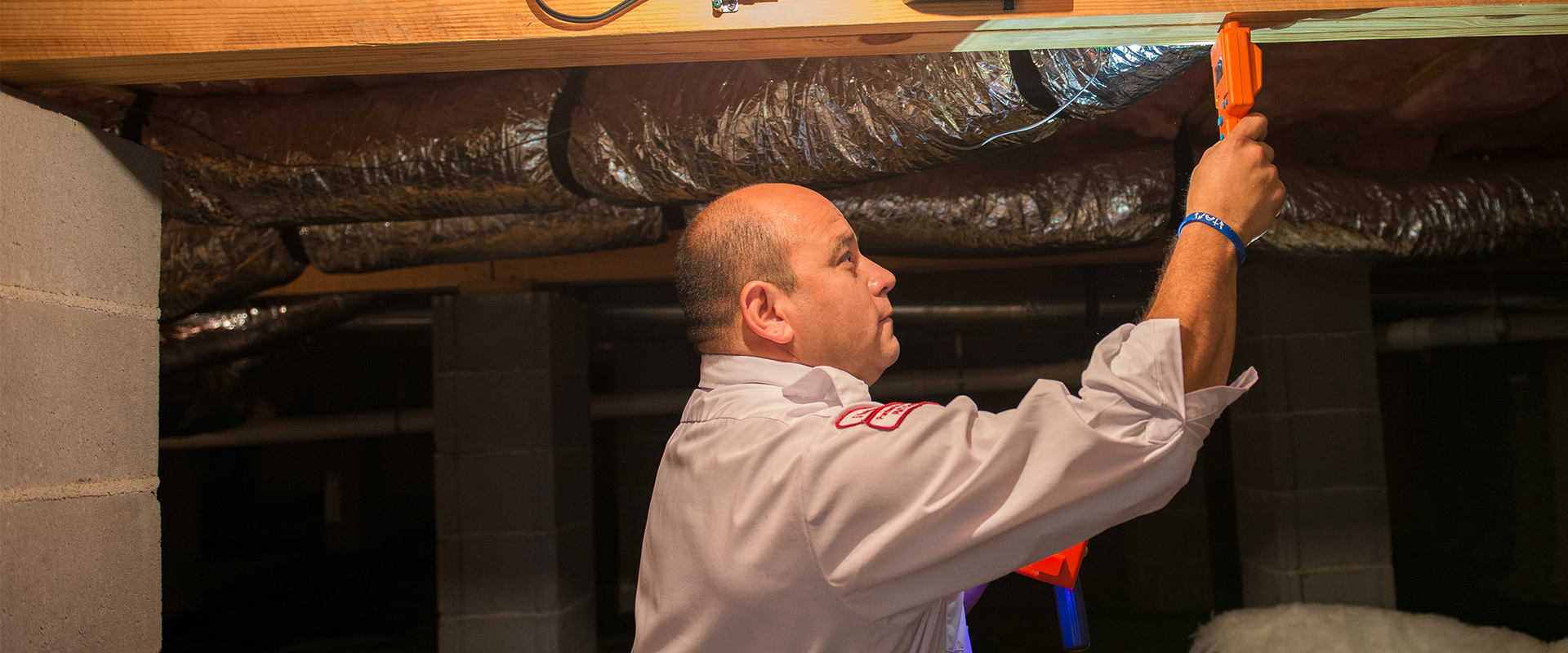 tech doing an inspection for moisture in a basement