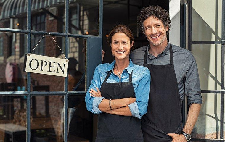 relieved business owners next to the open sign