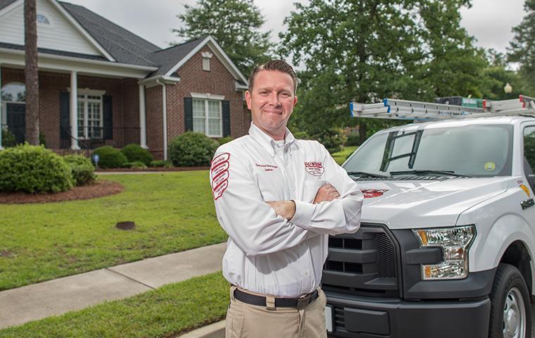 a hero shot of an aiken pest technician in front of truck