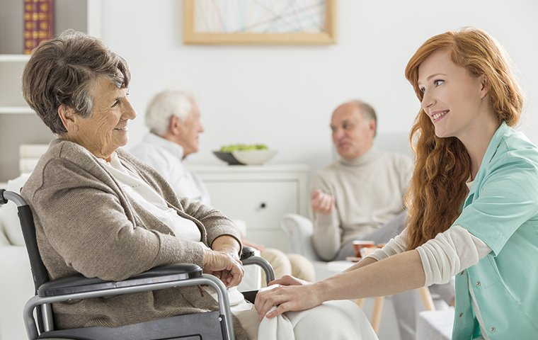 a nurse and elderly tenants inside of an assisted living facility