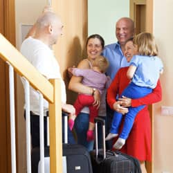 family being welcomed at door