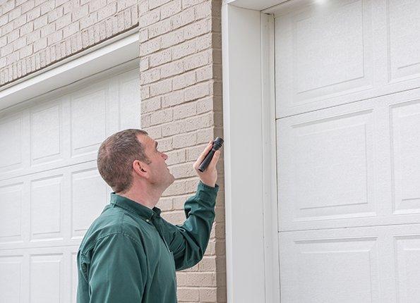 a technician checking exterior of home