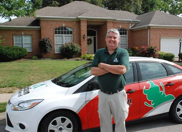 pest technician in front of company car