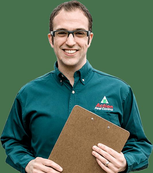 pest technician wearing black framed glass holding a clipboard