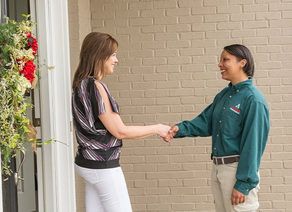 homeowner and technician greeting in front of house