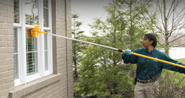 female pest technician sweeping the exterior of a residential building