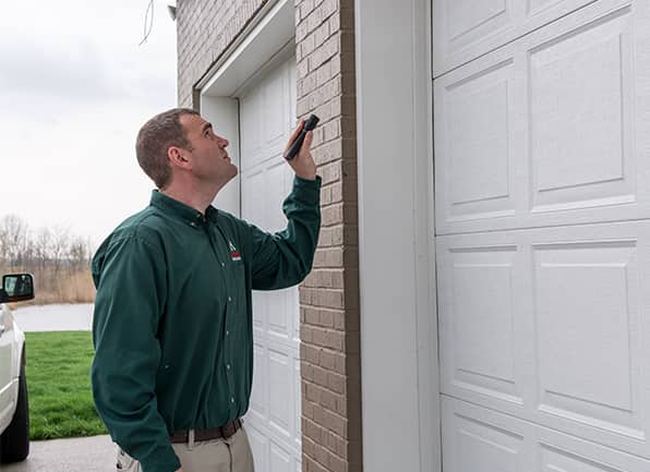 an action pest control technician inspecting the exterior of a home in nicholasville kentucky