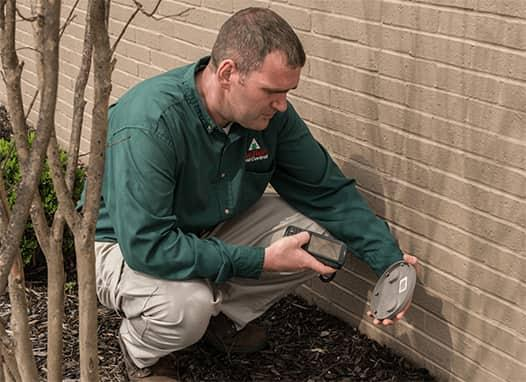 a male pest technician inspecting traps outside of a residence