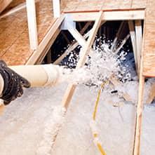 big blue bug technician spraying insulation in attic