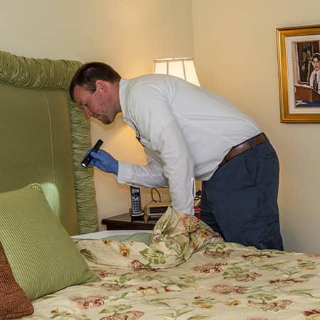 bed bug control technician inspecting a rhode island hotel room