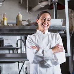 chef standing in front of kitchen with arms crossed