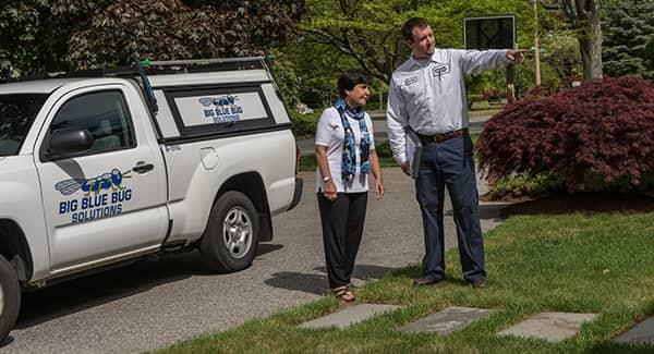 a view of a big blue bug solution technician walking a new england resident around their property while explaining the best pest control plan treatments available